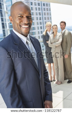 African American businessman and group of business men & women, businessmen and businesswomen team outside in modern city - stock photo
