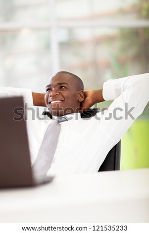 african american businessman daydreaming in office - stock photo