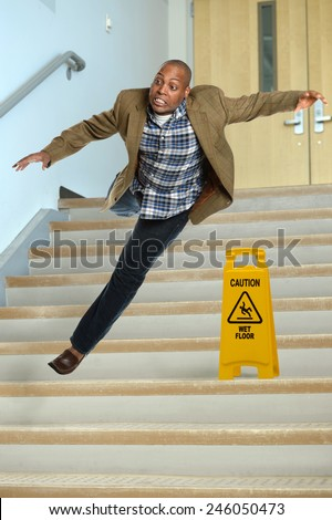 African American businessman falling on stairs with yellow warning sign on steps - stock photo
