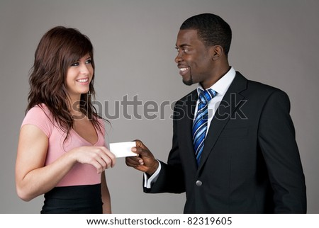 African American businessman giving his business card to a young Caucasian woman. - stock photo