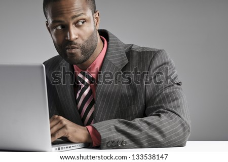 African American Businessman Looking Suspicious While Working On His Laptop - stock photo