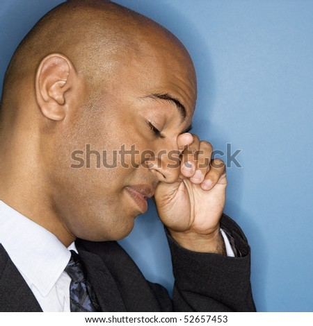 African American businessman rubbing his eyes. - stock photo