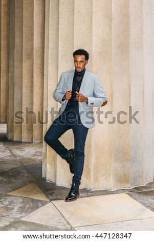 African American Businessman Semi-Formal Fashion in New York. Wearing gray blazer, unbuttoned,  blue pants, black leather boot shoes, a guy standing against columns outside office, looking forward.  - stock photo