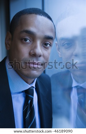 African-American businessman smiles towards the camera. His reflection can be seen in the window. Vertical shot. - stock photo