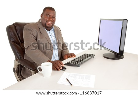 African American Businessman Smiling at the Camera While Sitting at his Desk - stock photo