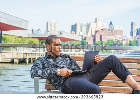 African American businessman traveling in New York. Wearing black flower patterned shirt,  young black guy sitting on chair by East River, reading, working on laptop computer. Brooklyn on background. - stock photo