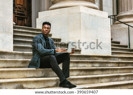 African American Businessman traveling, working in New York, wearing fashionable jacket, necktie, sitting on stairs outside office building, working on laptop computer. Instagram filtered effect.  - stock photo