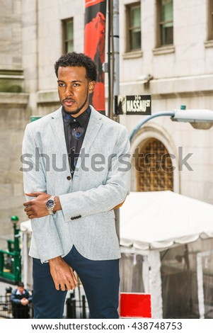 African American Businessman traveling, working in New York. Wearing gray patterned blazer, crossing arms, young black man with beard standing on street, seriously thinking, tough work ahead.   - stock photo