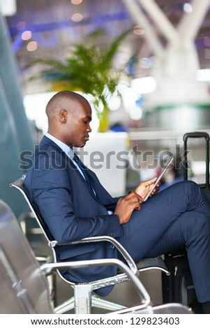 african american businessman using tablet computer at airport - stock photo