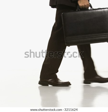 African American businessman walking carrying briefcase. - stock photo
