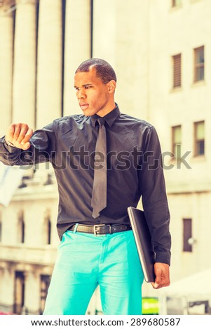 African American businessman with scar on head, standing on street in New York, looking at his wristwatch. Concept of self assured, self esteem, confidence and success, time to heal, time is money.  - stock photo
