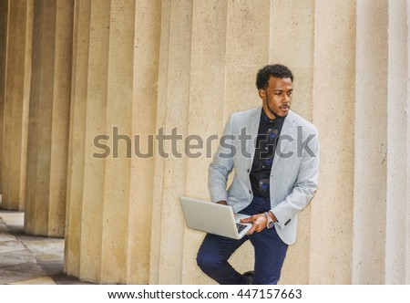 African American businessman working in New York, wearing gray blazer, blue pants, standing against columns outside office, reading, working on laptop computer during break, looking away, thinking. - stock photo