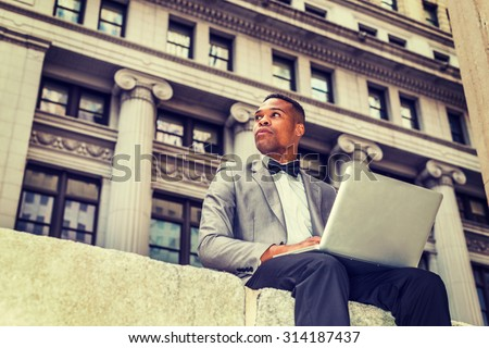 African American businessman working in New York. Wearing gray blazer, bow tie, young black man siting in business district, working on laptop computer. confidently looking away. Instagram effect. - stock photo