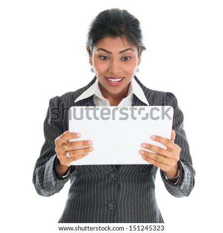 African American businesswoman looking at digital computer tablet with surprise face, isolated over white background. Mixed race Asian Indian and African American model. - stock photo