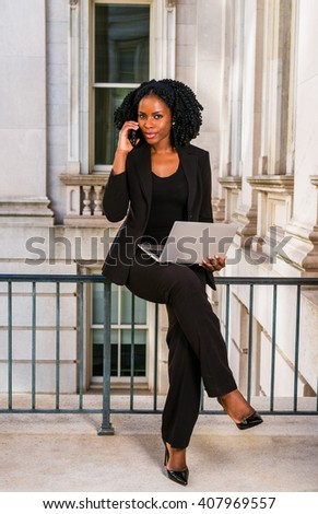African American Businesswoman working in New York. Young black college student with braid hairstyle sitting on railing in vintage style office building, working on laptop computer, making phone call. - stock photo
