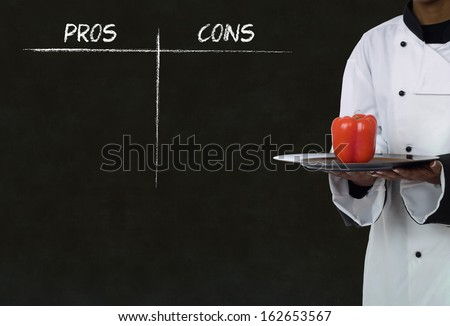 african american chef holding healthy food with chalk pros and cons on blackboard background - stock photo