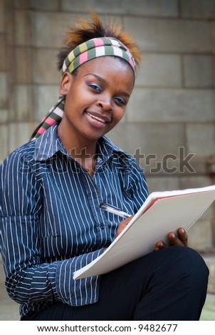 African American college student or office secretary PA taking notes - stock photo