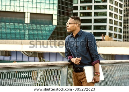 African American college student studying in New York. Wearing blue shirt, glasses, bracelets, holding laptop computer, a young black man standing in business district with high buildings, thinking.  - stock photo