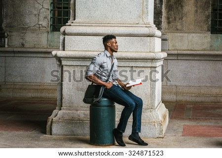 African American College Student studying in New York. Wearing gray shirt, jeans, cloth shoes, carrying shoulder leather bag, a black man sitting on metal pillar on street, reading book, thinking.  - stock photo