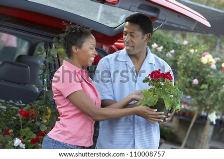 African American couple buying potted plant - stock photo