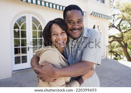African American couple hugging outdoors - stock photo