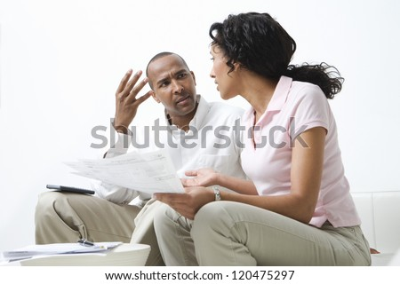 African American couple in discussion over excess domestic bills - stock photo