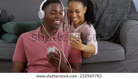 African American couple listening to music and taking picture with smart phones - stock photo