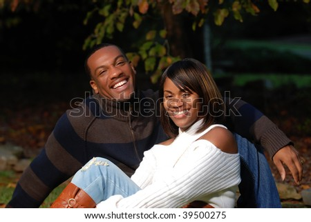 African-American Couple smiling sitting in the grass - stock photo
