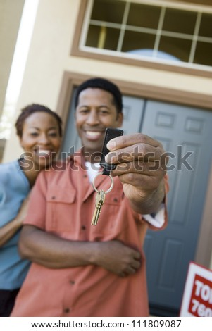 African American couple standing in front of a new home - stock photo