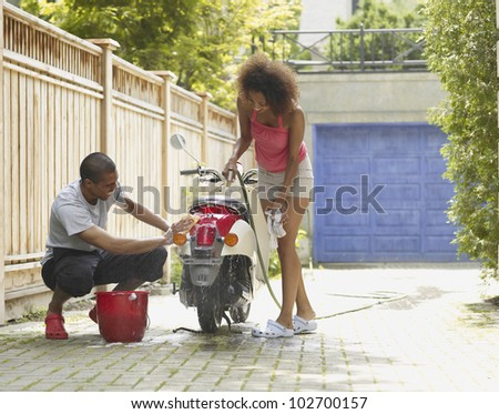 African American couple washing motor scooter - stock photo