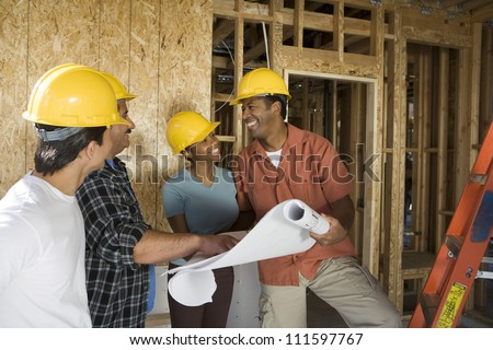 African American couple with blueprint at construction site - stock photo