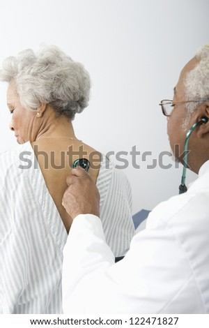African American doctor checking patient using stethoscope - stock photo