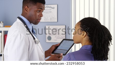 African American doctor taking patient history with tablet computer - stock photo