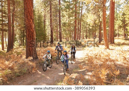 African American Family Cycling Through Fall Woodland - stock photo