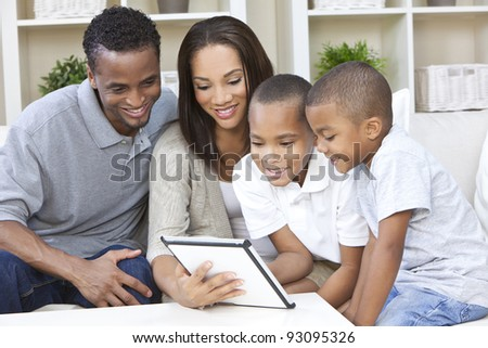 African American family, mother & father parents and two sons, having fun using a tablet computer together at home - stock photo