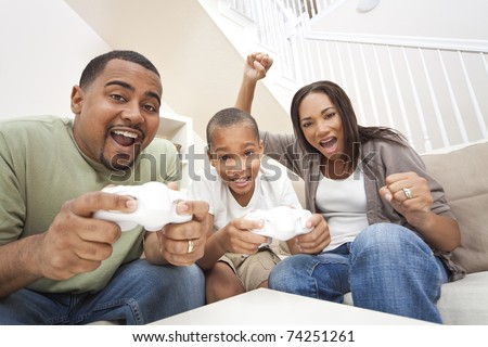 African American family, parents and son, having fun playing computer console games together, Father and son have the handset controllers and the mother is cheering the players. - stock photo
