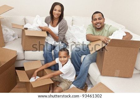 African American family, parents and son, unpacking boxes and moving into a new home, The adults are unpacking crockery and houseware. - stock photo
