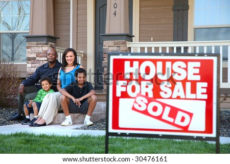 African American family sitting together on front steps of home with real estate sign in foreground - stock photo