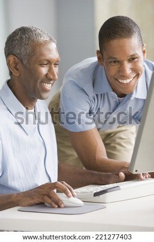 African American father and adult son looking at computer - stock photo