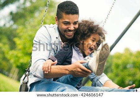 African American father and daughter having fun at the park - stock photo