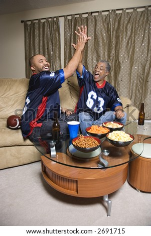 African-American father and son giving high five while watching football game. - stock photo