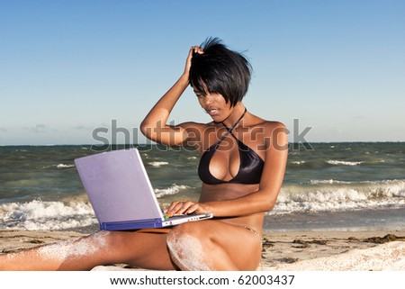 african-american female at beach on laptop  looking confused - stock photo