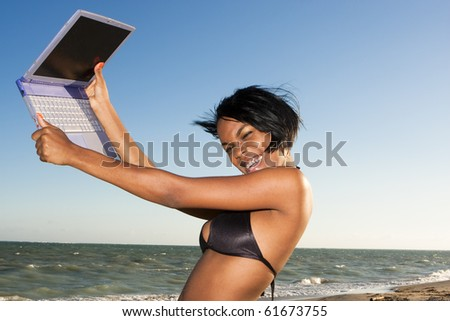 african-american female at the beach on laptop - stock photo