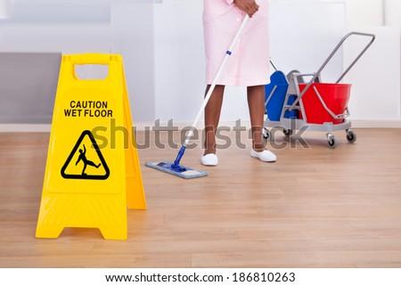 African American female housekeeper cleaning floor in hotel - stock photo