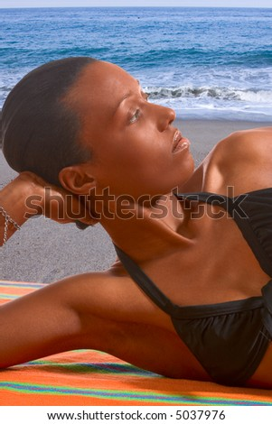 African-American female relaxing and taking sunbath by sea - stock photo