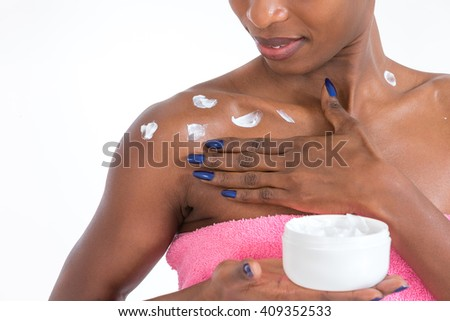 African American girl applying facial skincare product   - stock photo