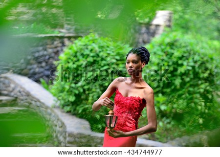 African American girl in a red dress, with dreadlocks, with a lamp and a candle in his hand, posing in the summer in the Park on a background of green plants. Portrait. Horizontal view - stock photo