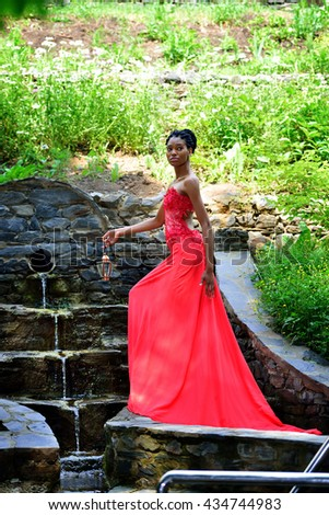 African American girl in a red dress, with dreadlocks, with lamp in hand, standing and posing on a Sunny day in the Park by the waterfall on the background of green plants and looking to the side. - stock photo