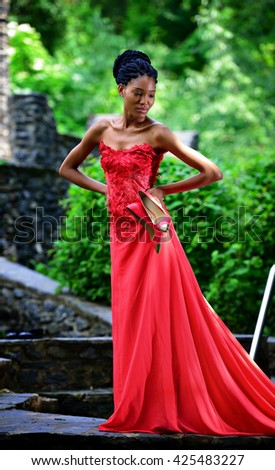 African American girl in a red dress, with dreadlocks, with red shoes in hand, posing in the summer in the Park on a background of green plants. Portrait. Vertical view - stock photo