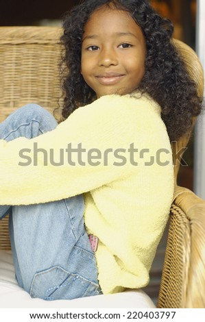 African American girl sitting in chair - stock photo